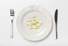 Pills on a plate on a white background Stock Images