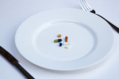Pills on a plate. Pills on a white plate with cutlery Royalty Free Stock Images