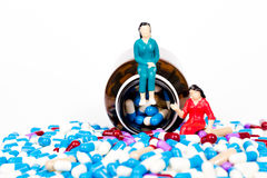 Pills pouring out of the brown bottle with miniature people Royalty Free Stock Photography