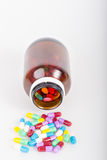 Pills pouring out of  brown bottle Royalty Free Stock Images