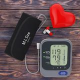 Pills and Red Heart near Modern Digital Blood Pressure Measureme. Nt Monitor Equipment on a wooden table. 3d Rendering Royalty Free Stock Photos