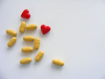 Pills and red hearts isolated with place for writing. Pills and red hearts on white background with place for writing Royalty Free Stock Photo