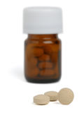 Pills. Round tablets and brown small bottle on white background Stock Images