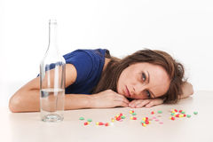 Pills scattered on table with bottle on white background. Royalty Free Stock Photo