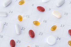 Pills on a schedule. Close-up of pills on a daily and weekly calendar schedule stock photo