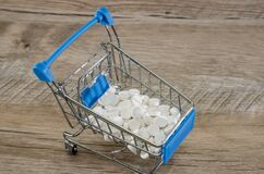 Pills in a shopping cart on a wooden background.