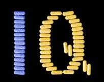 Pills spelling IQ. Colourful pills spelling the acronym IQ isolated on black stock image