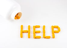 Pills spelling word help. Orange medicinal pills spilling out of bottle spelling word help, white background royalty free stock image