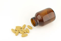 Pills spilling from bottle Stock Images