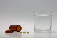 Pills spilling. From bottle and a glass of water royalty free stock photos