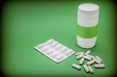 Pills Spilling From An Open Bottle On Green Background Royalty Free Stock Image