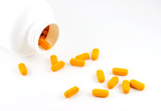 Pills spilling out of bottle Royalty Free Stock Images