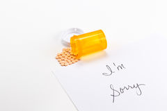 Pills spilling out of medicine bottle with I'm Sorry note, implication suicide overdose Royalty Free Stock Images