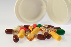 Pills spilling out from medicine box Royalty Free Stock Images