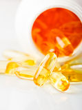 Pills spilling out of pill bottle. Shiny yellow vitamin e fish oil capsule  spilling out of pill bottle Stock Images