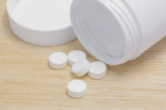 Pills spilling out of pill bottle on wood back ground Royalty Free Stock Images