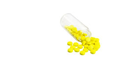 Pills spilling out of pill bottle. Yellow Pills spilling out of pill bottle isolated on white background Stock Photo