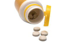 Pills spilling out of a prescription bottle. On white background Stock Photography