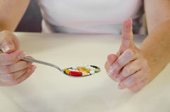 Pills on spoon. Human hand with spoon full of colorful medicals Stock Photos