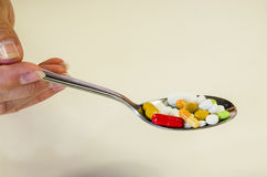 Pills on spoon. Human hand with spoon full of colorful medicals Royalty Free Stock Photo