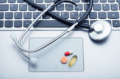 Pills and stethoscope on laptop Royalty Free Stock Photos