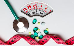 Pills stethoscope measuring tape on scales. Health care Royalty Free Stock Images