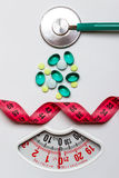 Pills stethoscope measuring tape on scales. Health care Stock Photos