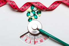 Pills stethoscope measuring tape on scales. Health care Stock Photography