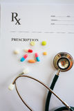 Pills and stethoscope on prescription. Pills and stethoscope on a prescription Stock Photo
