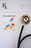 Pills and stethoscope on prescription. Pills and stethoscope on a prescription Royalty Free Stock Images