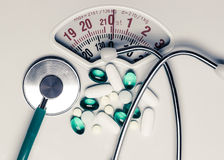 Pills and stethoscope on scales. Health care Royalty Free Stock Photography