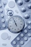Pills and stopwatch Stock Images