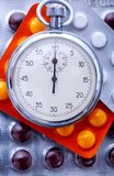 Pills and stopwatch Stock Image