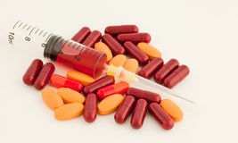 Pills and syringe. Pills, tablets and caplets with covered syringe Stock Photography