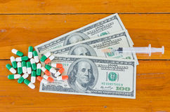 Pills and syringe on hundred U.S. dollars on wood background Stock Photos