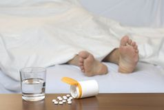 Pills on the table. Pills and a glass of water on the table. Sleeping person in the background Stock Images