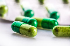 Pills. Tablets. Capsule. Heap of pills. Medical background. Close-up of pile of yellow green  tablets Stock Photo