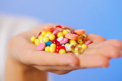 Pills, tablets and drugs heap in doctor's hand. On blue background Royalty Free Stock Image