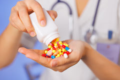 Pills, tablets and drugs pouring from bottle. In doctor's hand on blue background Stock Photo