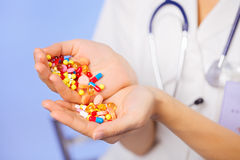 Pills, tablets and drugs pouring in doctor's hands. On blue background Stock Image