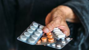 Pills and tablets in hand of old woman, selective focus Royalty Free Stock Photos