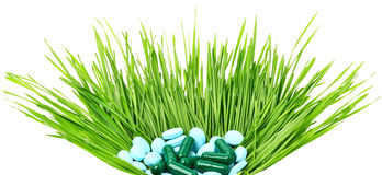 Pills, tablets and wheat grass in the basket Stock Photos