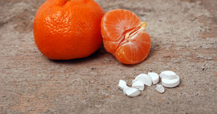 Pills and tangerine on wood backgorund Stock Photography