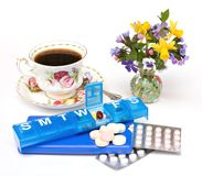 Pills, Teacup, Flowers. A still life scene with teacup, vase of spring flowers, assorted pills, drugs, vitamins, and dispensers royalty free stock images