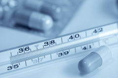 Pills and thermometer Royalty Free Stock Images
