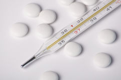 Pills and a thermometer Stock Photos