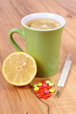 Pills, thermometer and hot tea with lemon for colds, treatment of flu and runny Stock Photo