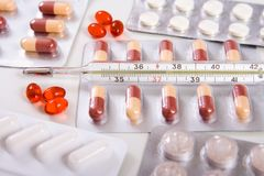 Pills and thermometer. Vitamins, capsules pills and thermometer with heat temperature Royalty Free Stock Photo