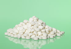 Pills toward green background. Stack of pills towards green background, pills, medical treatment, white, lozenge, tablet, pastille, pastil, drugs, curative Stock Photography