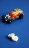 Pills and toy car on blue Royalty Free Stock Image
